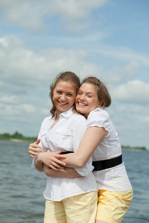 twins girls hugging and laughing with one best man on the shore photo