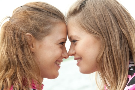 identical: girl twins look at each other in the eye to eye Stock Photo