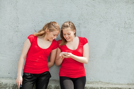 Twin girls in red with phones photo