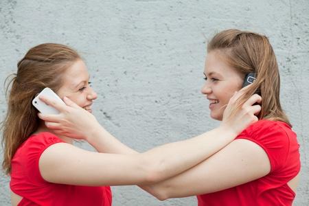 ni�as gemelas: Muchachas gemelas en rojo con tel�fonos