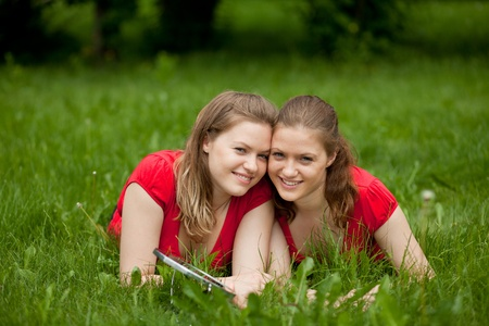 girl twins lie in the grass and relax photo