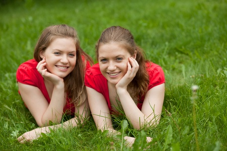 twin sister: girl twins lie in the grass and relax