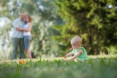 vater und baby: Familie von drei Menschen im Park spazieren