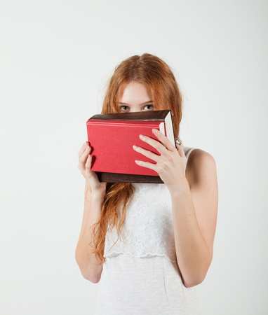 Girl hiding behind the books photo