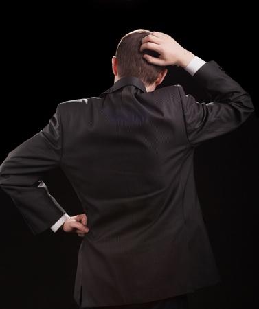 Junger Mann in einem Anzug , der seinen Kopf in Verwirrung anstarrt Standard-Bild