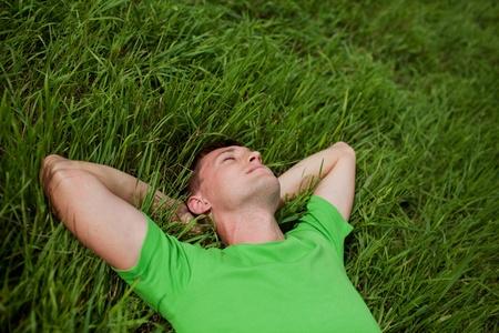 젊은 남자가 그의 머리 뒤 그의 손으로 잔디에 누워