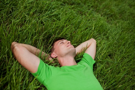 young man lying on the grass with his hands behind his head Banco de Imagens