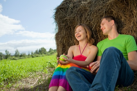 couple with apples sitting on the grass photo