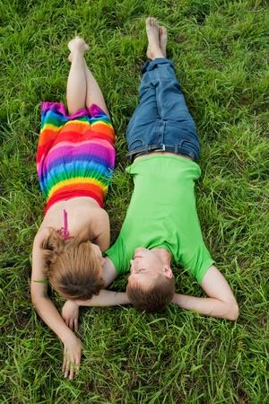 Couple lying on grass and enjoys photo