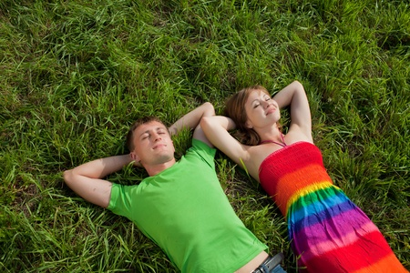 Couple lying on grass and enjoys photo