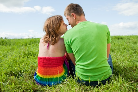 people sitting: Couple on the grass looking at each other