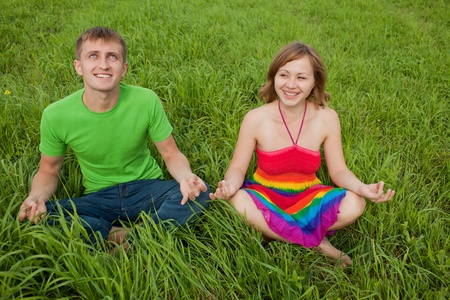 Couple on the grass and meditate together smiling photo