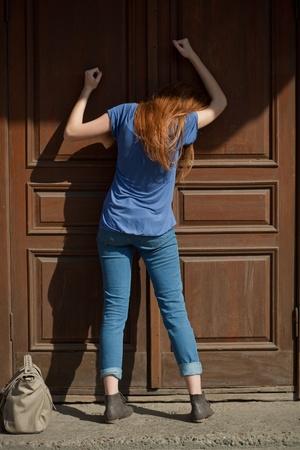 그녀는 문을 세게 친다 스톡 사진