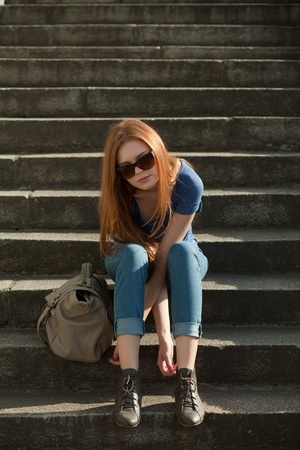 red-haired girl sitting on the stairs with a bag Stock Photo