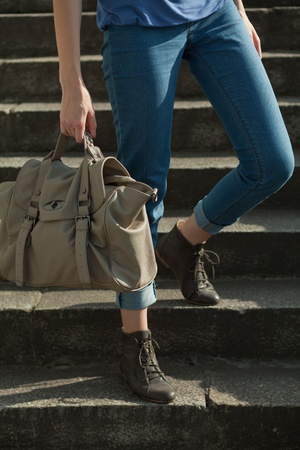 feet girl holding a bag on the stairs Stock Photo