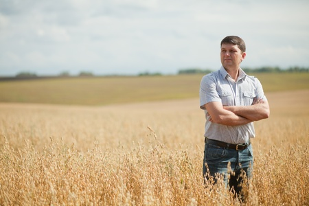 農家: 作物のフィールドを検査する所有者