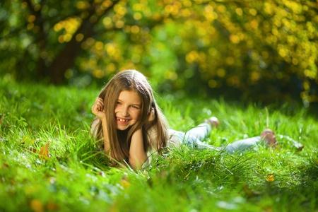 가을 공원에서 잔디에 소녀