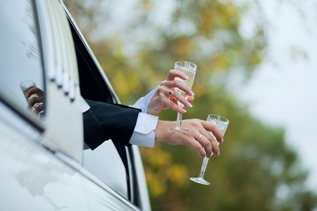 hands with glasses of champagne lean out the car window