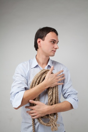 young man with a rope in his hands looking away