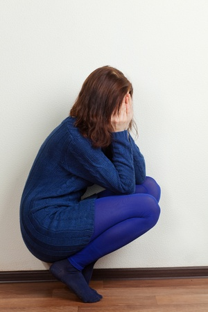 sad crying girl in the blue squatting photo