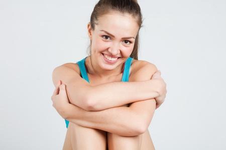 hugging knees: pretty athletic girl sitting hugging her knees