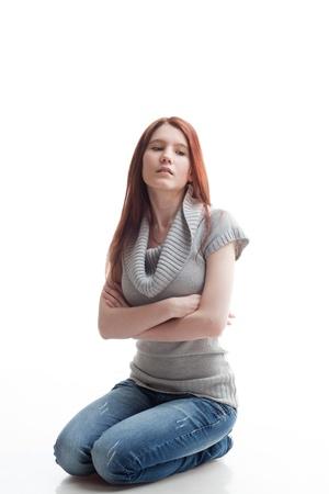 en cuclillas: chica sobre un fondo blanco reflexivo en cuclillas Foto de archivo