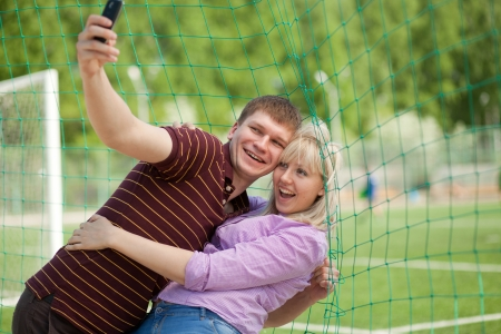 boy and girl photographed themselves on the phone and laughing photo