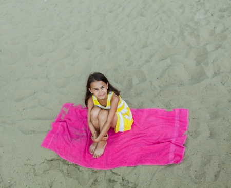 five-year-old girl lying on the beach photo
