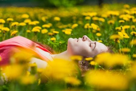 beautiful girl lying on the field of dandelions