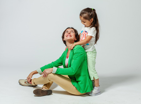daugther: Daughter hugging her mother who is sitting on the floor