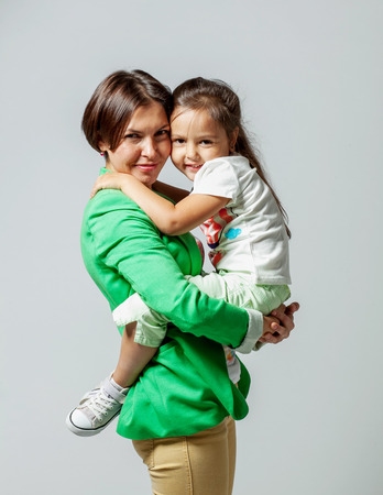 daugther: Daughter hugging her mother sitting in her arms Stock Photo