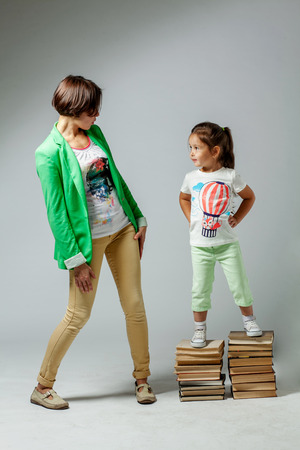 daugther: Mom and daughter standing on a pile of books Stock Photo