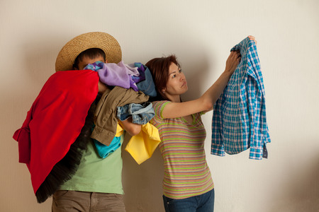 couple parses a bunch of clothes in the studio photo