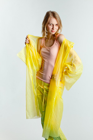wet t shirt: blonde girl in yellow raincoat standing parted