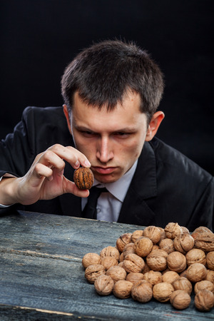 young man looking at a nut selected from a pile of nuts