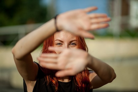 beautiful red-haired girl closes hands from the sun Stock Photo