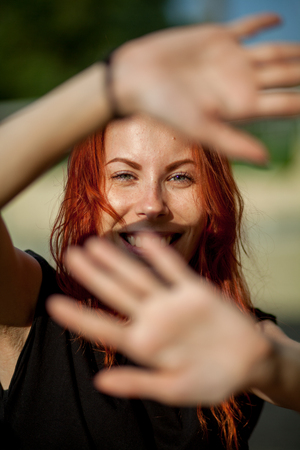 secrete: beautiful red-haired girl closes hands from the sun Stock Photo