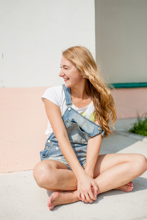 girl against a wall sits cross-legged and laughing