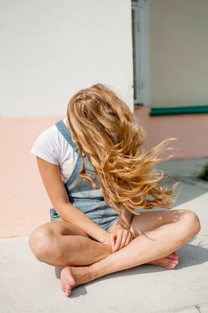 girl against a wall sits cross-legged and laughing Stock Photo