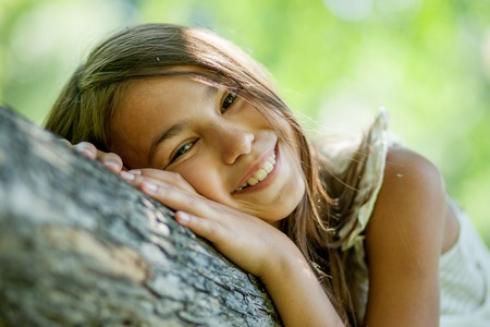 face in tree bark: Happy young girl sitting in a tree