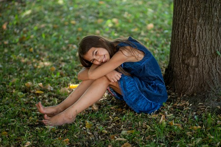 little girl sitting at a tree in a blue dress Stock Photo