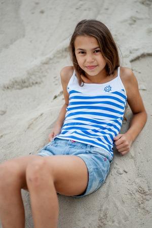 striped vest: Girl in striped vest sits on sand and enjoys