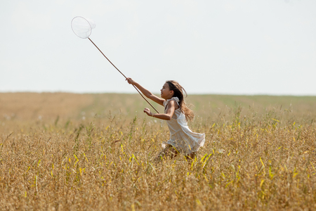 Girl in white running on the field with a net Stock Photo