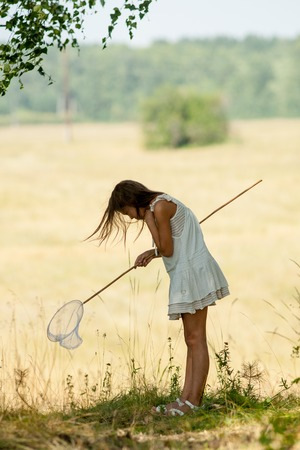 girl in a white dress looks for insects