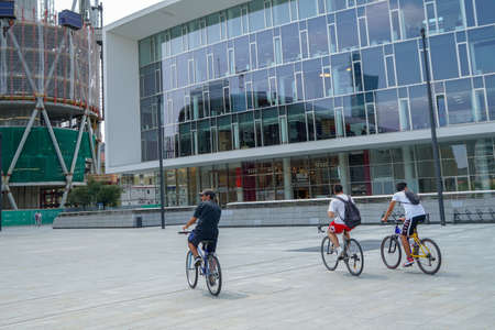 Milan, teenagers in on bikes in the business center of Porta Nuova almost empty because of smart working and crisis is perfect now for bicycling