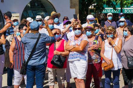 Saintes Maries de la Mer - 09/04/2020: Saintes Maries de la Mer - 09/04/2020: tourists wearing mask protection listening to a guide