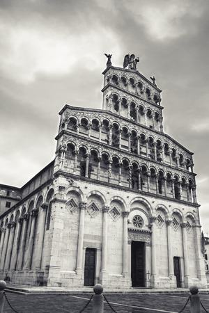 or san michele: San Michele in Foro, built over the ancient Roman forum, is an ancient church. The facade has a large series of sculptures and inlays, numerous of which remade in the 19th century. Black and white and clouds create a drammatic view of this church Stock Photo