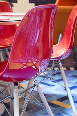 Essaouria, Morocco - September 2017: Red plastic chair ouside of cafe reflecting star deisgn in floor mosaic  에디토리얼