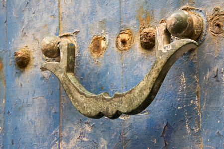 Essaouria, Morocco - September 2017: Ancient rusted door knocker on door with faded blue paint