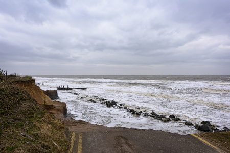 UK, HAPPISBURGH - 18 MAR 2018: Coastal errosion taking place duirng a winter storm. Many homes have recently been lost in this community due to coastal erroasion.